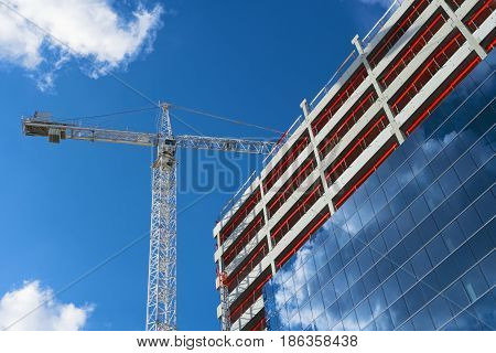 Tower crane and modern building under construction. Industrial construction crane. New residential development. Construction site on blue sky background