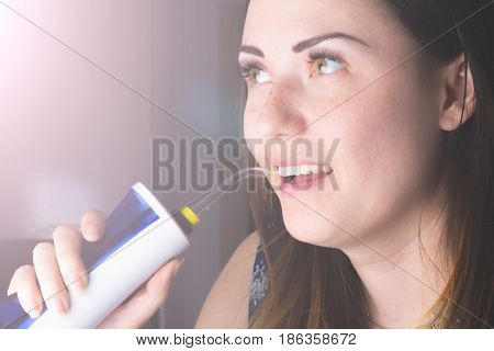 A woman using an oral irrigator in bathroom.