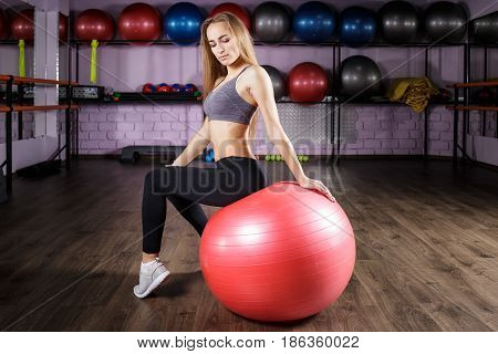 Young beautiful fitness girl sitting on fitness ball in health club. Blonde sporty woman in the gym