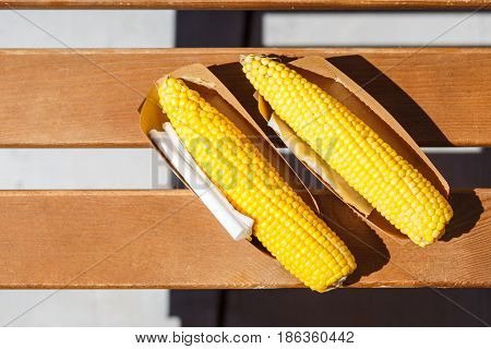 Two boiled salted corn on the cob in paper box. Beach fast food background top view