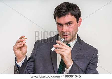 Businessman Is Comparing Electronic Cigarette And Tobacco Cigare