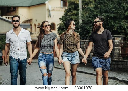Summer Leisure Of Happy, Smiling Friends Walking Along Brick Road