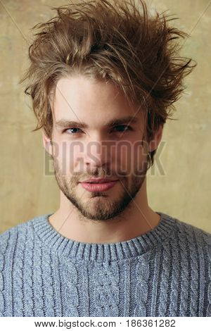 hairdressing. Handsome bearded man with beard or sexy caucasian macho on beige wall background. Stylish blond hair haircut and young unshaven face skin. Male beauty and hairdressing.