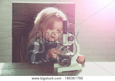 student boy with microscope study science at educational workplace makes experiment