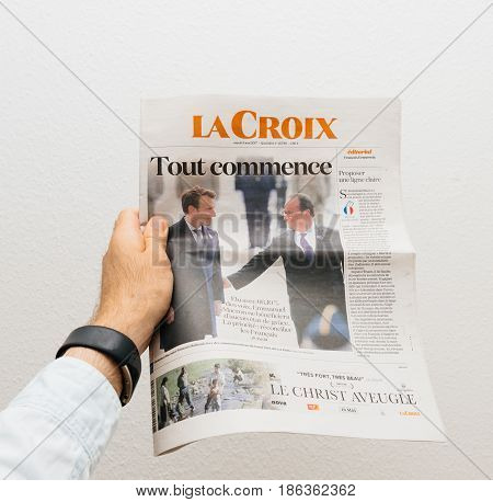 PARIS FRANCE - MAY 10 2017: Man holding La Croix newspaper front page against white background with the picture of the newly elected French president Emmanuel Macron the 8th President of France