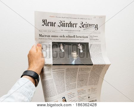 PARIS FRANCE - MAY 10 2017: Man holding Neue Burcher Zeitung newspaper front page against white background with the picture of the newly elected French president Emmanuel Macron the 8th President of France