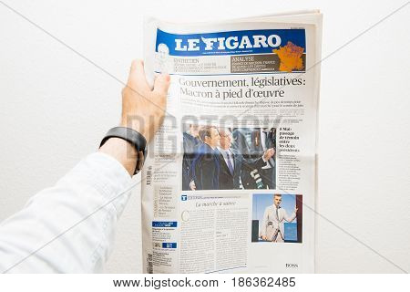 PARIS FRANCE - MAY 10 2017: Man holding Le Figaro newspaper front page against white background with the picture of the newly elected French president Emmanuel Macron the 8th President of France