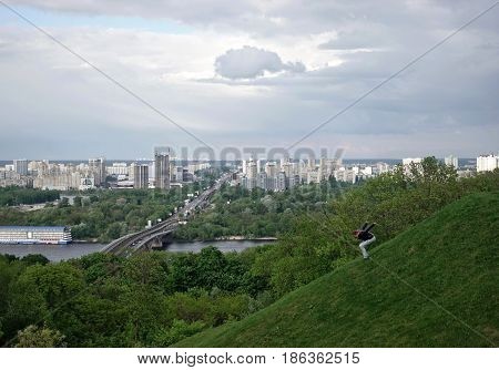 KIEV - UKRAINE - MAY 2017: Glory Park in Kiev.The girl descends from the slope on the background of the left bank of Kiev
