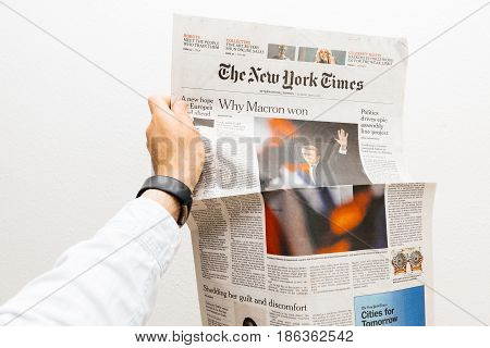 PARIS FRANCE - MAY 10 2017: Man holding The new york Times newspaper front page against white background with the picture of the newly elected French president Emmanuel Macron the 8th President of France