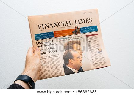 PARIS FRANCE - MAY 10 2017: Man holding Financial Times newspaper front page against white background with the picture of the newly elected French president Emmanuel Macron the 8th President of France