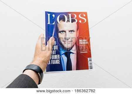 PARIS FRANCE - MAY 10 2017: Man holding L'Obs magazine newspaper front page against white background with the picture of the newly elected French president Emmanuel Macron the 8th President of France