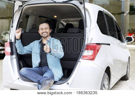 Portrait of Afro man showing thumb up while holding a car key and sitting on the back his new car in the showroom