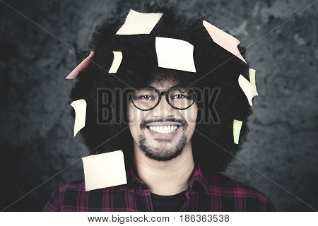 Close up of a young Afro man with casual clothes smiling at the camera while wearing glasses with sticky note on his curly hair