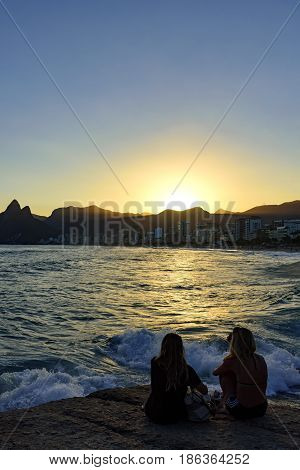 Girls on the stone looking at the sea during sunset on Ipanema beach Rio de Janeiro with Twoo Brothers hill and Gavea Stone in background