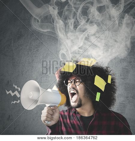 Young Afro man looks angry and shouting with a megaphone shot with empty sticky notes and smoke on his curly hair