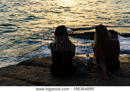 Girls on the stone looking at the sea during sunset on Ipanema beach Rio de Janeiro