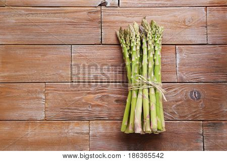 Bunch Of Green Asparagus On Brown Wooden Table