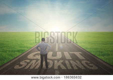 Back view of Asian man wearing casual clothes while standing with a quit smoking word on the road