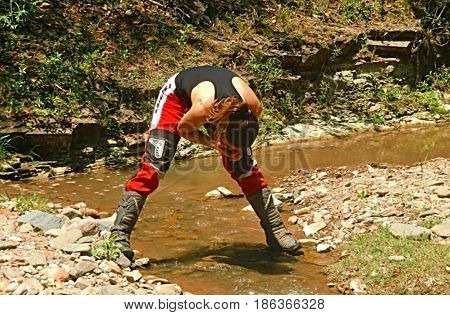 TUCUMÁN, ARGENTINA - OCTOBER 18, 2014: Biker woman refreshing herself with water at the stream. Sunny day at the hills, heat is unbearable.
