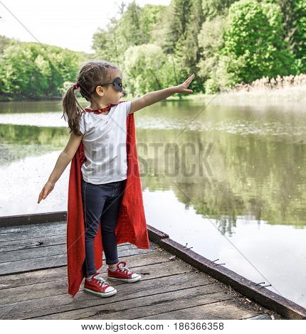 little cute girl in costume of a super hero plays in the fresh air near the river on the wooden pierthe concept of a super hero and a childhood dream