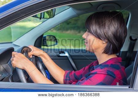 Colombian woman behind steering wheel in car