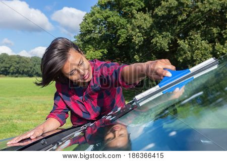 Colombian woman cleaning car windshield in nature