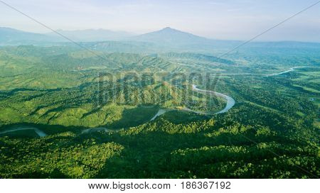 Beautiful top view of mountain landscape with a river green forest and villages. Shot in Majalengka West Java Indonesia