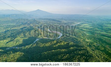Beautiful bird view in mountain valley with a river green forest and villages. Shot in Majalengka West Java Indonesia
