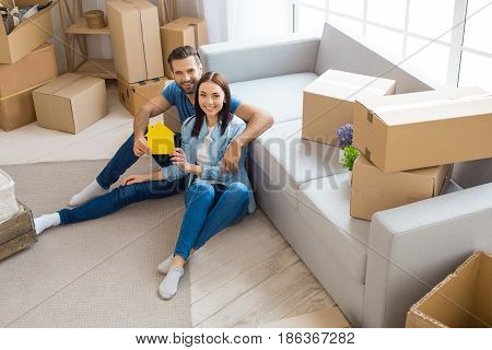 Young couple man and woman moving to a new apartment together relocation holding house shape paper