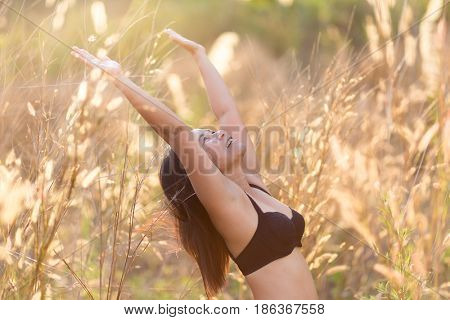 Asian woman enjoying sunlight and relaxing in a field