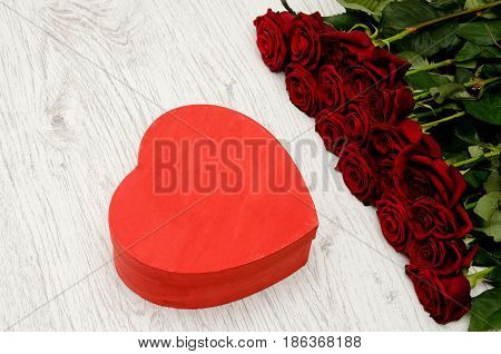 Red box in the heartshaped and roses on a white wooden background top view