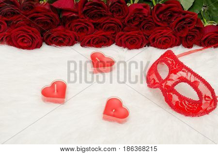 Red carnival mask and candles of heartshaped on a wooden table on a background of scarlet roses