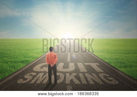 Image of young businessman looking at the sunbeam while standing with text of quit smoking in the highway