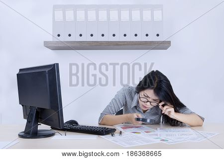 Portrait of a beautiful businesswoman looks serious while checking a declining chart with a magnifying glass
