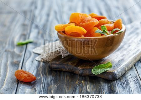 Dried Apricot Fruits In A Wooden Bowl.