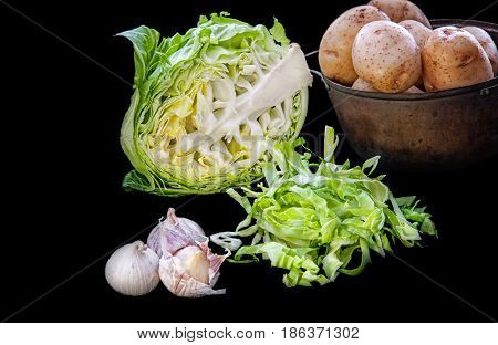 green cabbage half head half cut into strips for a salad with the potatoes in a pot and heads of garlic on a black isolated background.