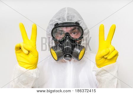 Man In Coveralls With Gas Mask Is Showing Victory Symbol