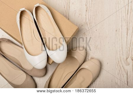 Women shoes (ballet flats) white and beige on a light wooden background. Selective focus.