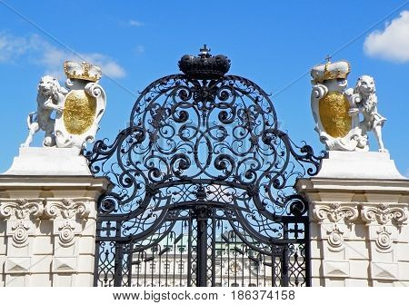 Gorgeous wrought iron gate and pair of lion sculptures against vivid blue sky, Vienna, Austria