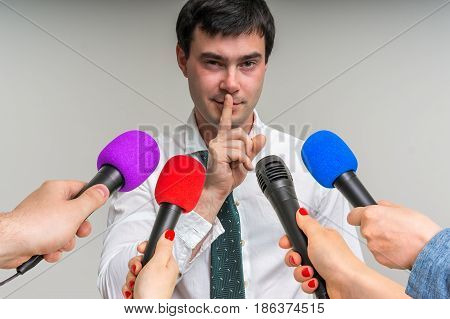 Reporters with microphones making interview with handsome man - journalism and broadcasting concept