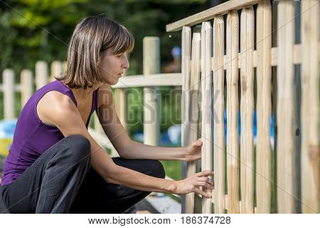 Woman Building A Garden Fence