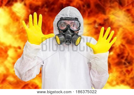 Man in coveralls with gas mask is showing stop gesture - nuclear and biohazard concept
