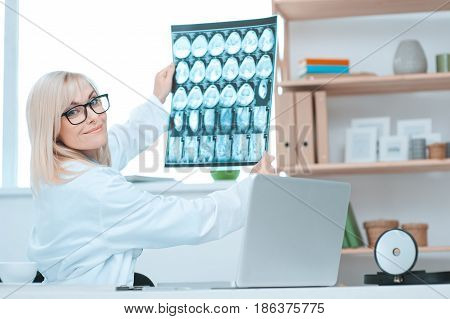 Young woman doctor sitting in the office at hospital looking x-ray