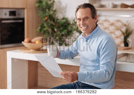 Business papers in my hands . Delighted smiling intelligent pensioner sitting in the kitchen while enjoying cup of coffee and reading important documents