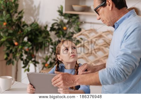Demonstrating lack of time for electronic games. Caring aging confident grandfather standing at home while taking away digital device from granddaughter and upbringing little kid