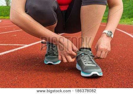 Woman Is Lacing Her Shoes On A Stadium Running Track