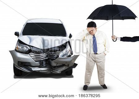 Insurance concept of car insurance. Dented car with overweight businessman looks confused under umbrella isolated on white background
