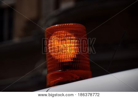 Close view on orange rotating lite related to construction work