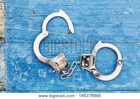 metal chrome handcuffs on blue wooden background