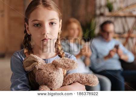 Without care and attention. Sad confused little girl waiting for parents attention at home and holding toy while adults using devices and paying no attention in the background